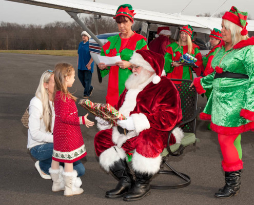 Santa and Elves distribute presents at the 2015 Santa Fly-In